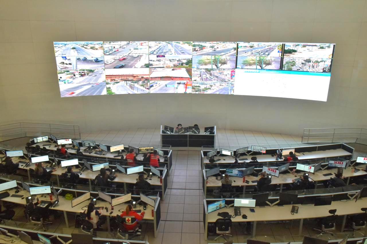 Contiene imagen interior, pantallas vigilancia, escritorios, personas