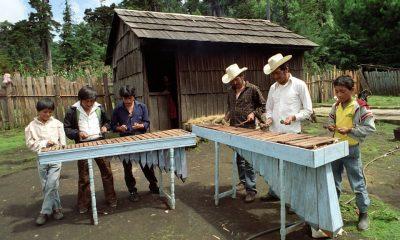 Contiene imagen exterior, hombres, niños, instrumento musical marimba, choza