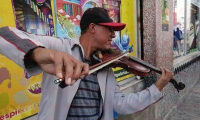Contiene imagen exterior hombre con gorra tocando violín